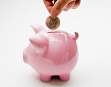 Hand_Putting_Deposit_Into_Piggy_Bank_(5737295175).jpg